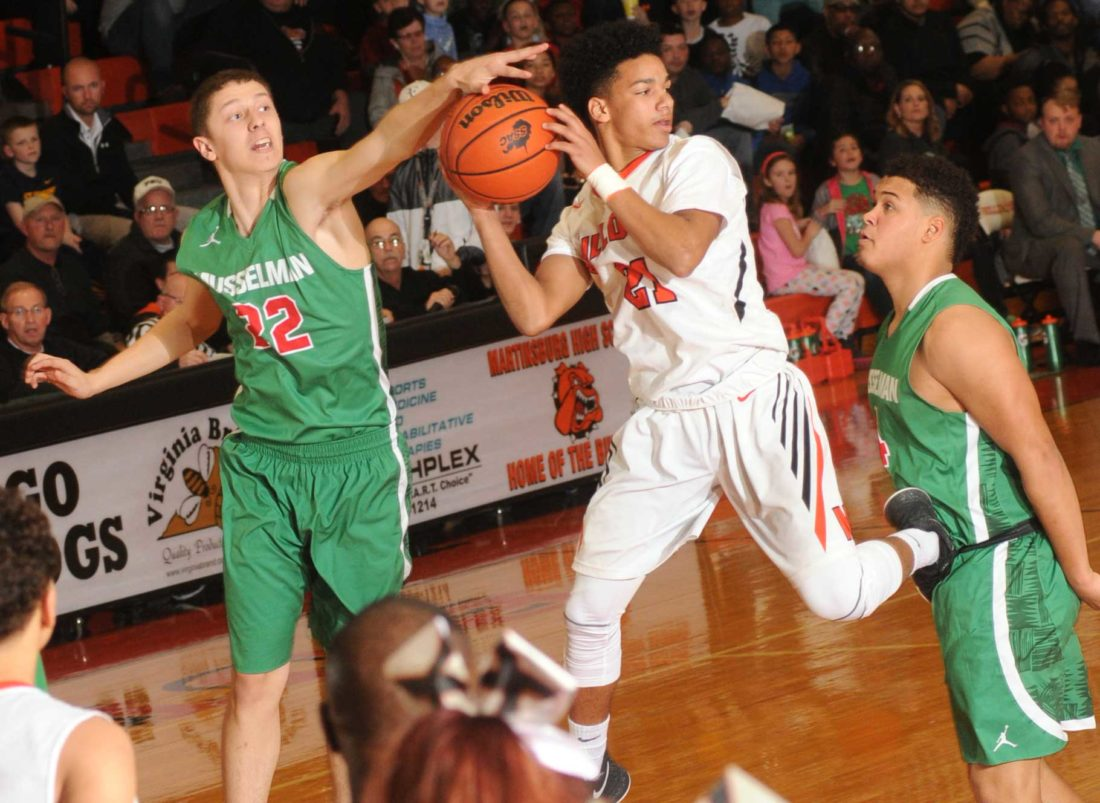 Musselman's Devon Caton, left, and Latrell Warr, right, force Martinsburg's Jarod Bowie  into an errant pass during third-quarter action of the Region II, Section 1 championship on Friday night in Martinsburg.