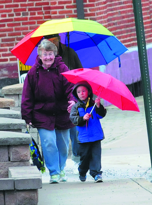 Journal photo by Ron Agnir Jax Riggleman, 4, and his grandmother, Sandra Riggleman, walk home in the rain along South Waters Street on Monday afternoon.