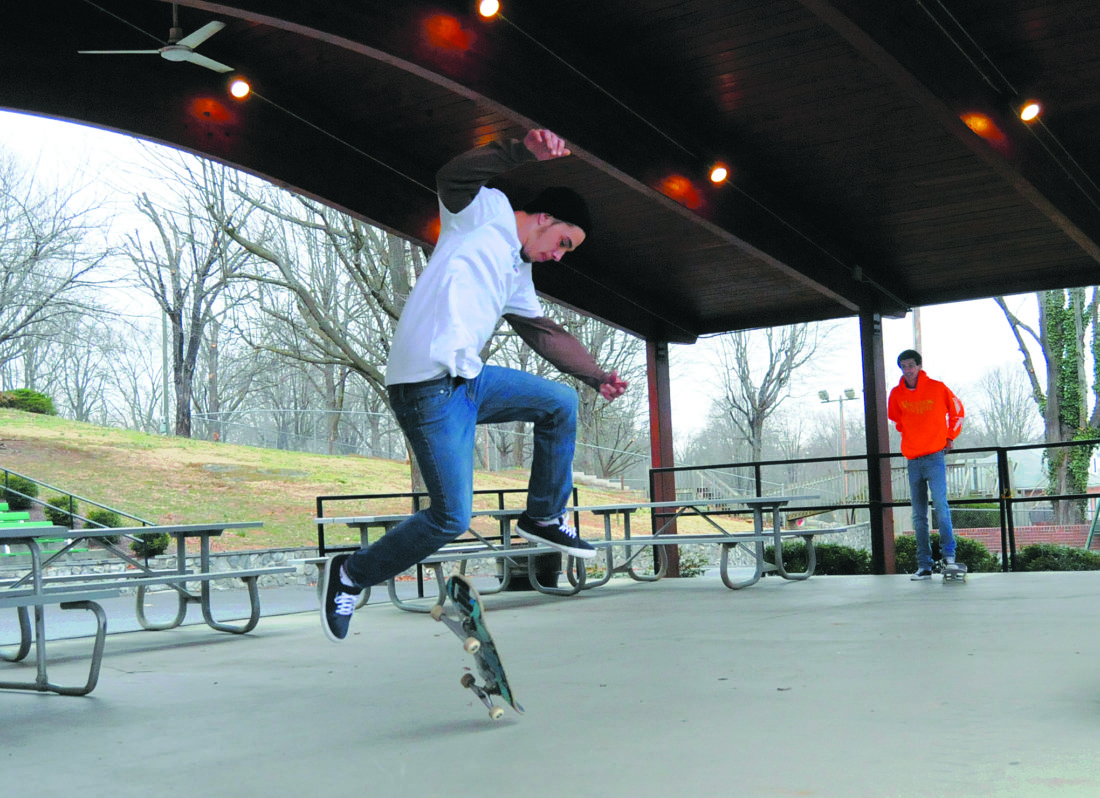 Journal photo by Ron Agnir Skateboarder Jordan Marple, left, works on landing a half cab flip trick as Isiah Finley watches and waits his turn on a rainy day under the main pavillion at War Memorial Park in Martinsburg.