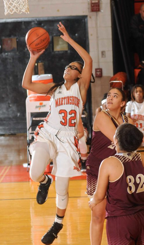 Martinsburg's Cameron Awkard, left, slips past Jefferson's  Kiayha Bradley, center, and Tori Banjoman during the fourth quarter of their Class AAA, Region II co-finals game (Journal photo by Ron Agnir)