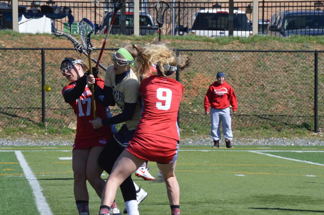 Shepherd's Courtney Matthews loses the ball under pressure from Edinboro's Rachel Olson, left, and Elysia Garland. (Journal photo by Jessica Manue)