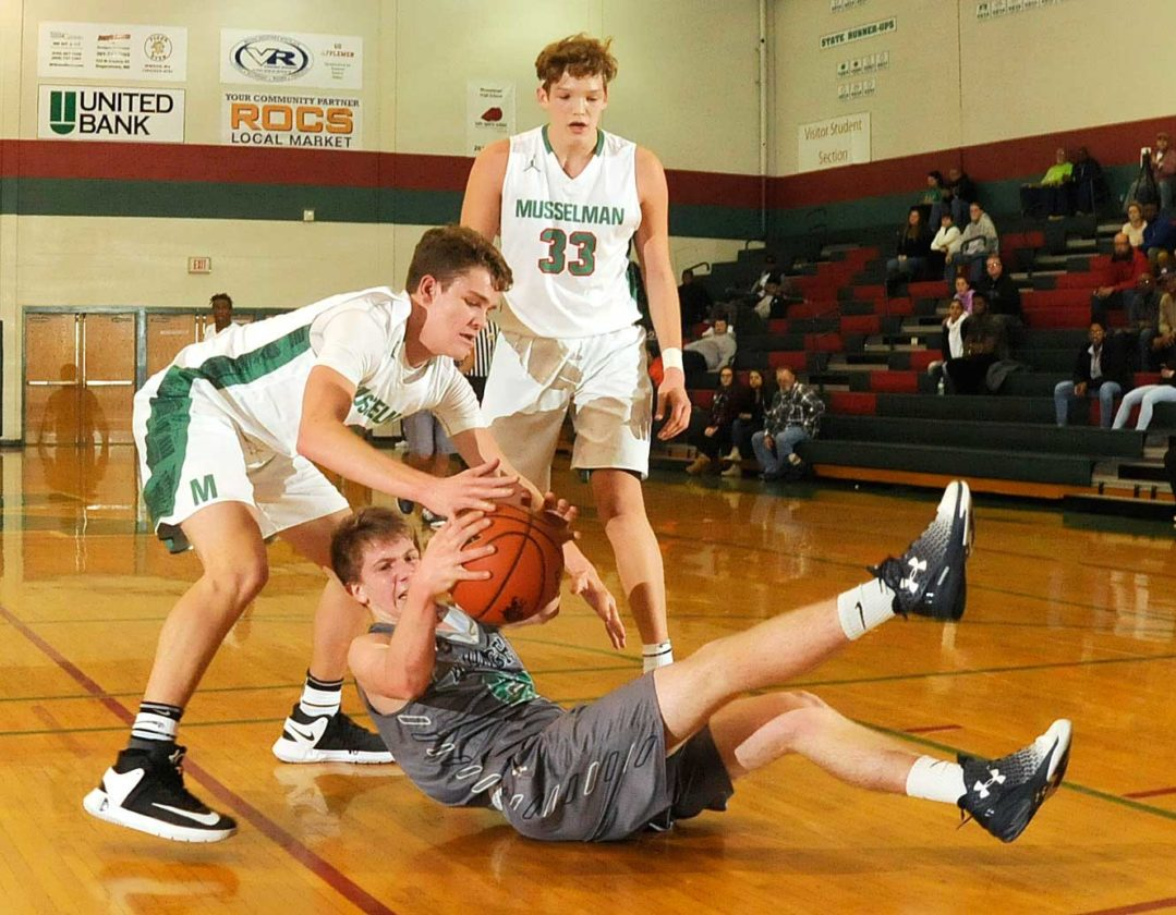 Journal file photo by Ron Agnir Musselman's Cam Stephens, left, scraps with Woodgrove's Alex Owens for a loose ball as Jake Stephens watches during the third quarter of their game.