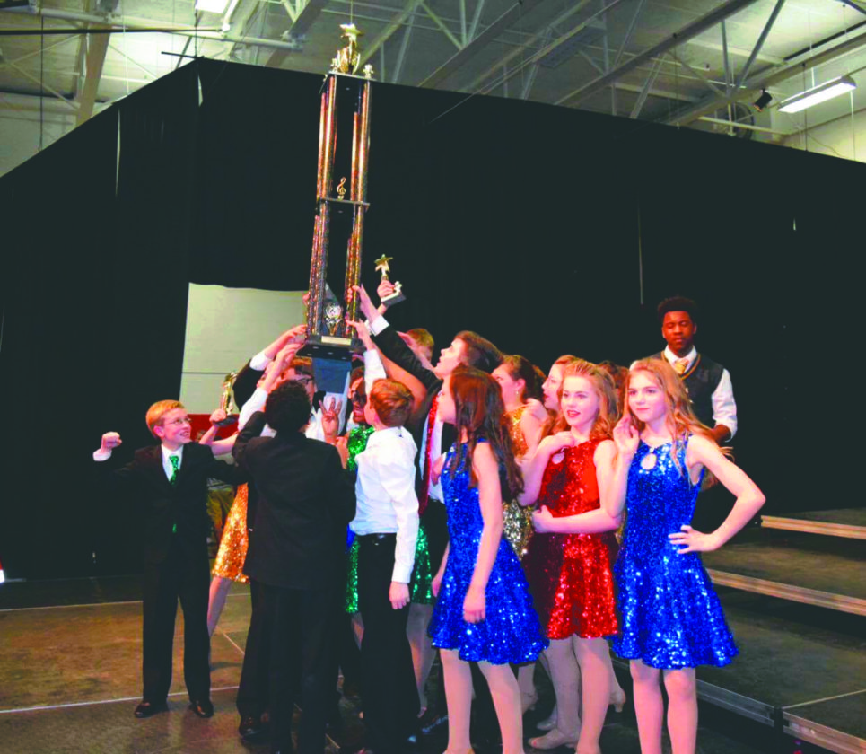 Members of the South Middle School show choir celebrate with the trophy for their state championship at Hurricane High School on Friday. (Submitted photo)