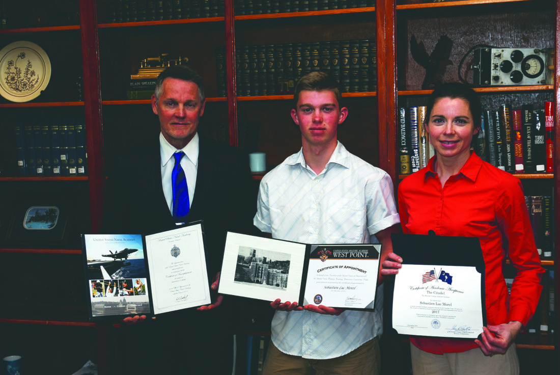 (Journal photo by Jeff McCoy) Kenneth and Geneva Morel stand with their son Sebastien, center, while holding college acceptance awards from the Citadel, West Point Military Academy and the Naval Academy.