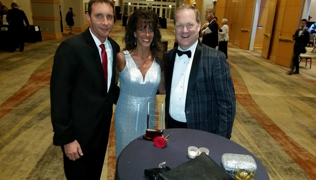 Shown, from left. are Coldwell Banker Premier's Steve DuBrueler, CEO and Holli Kudlak, relocation coordinator, after receiving the Platinum Award from Charlie Young, president  and CEO of Coldwell Banker. (Submitted photo)