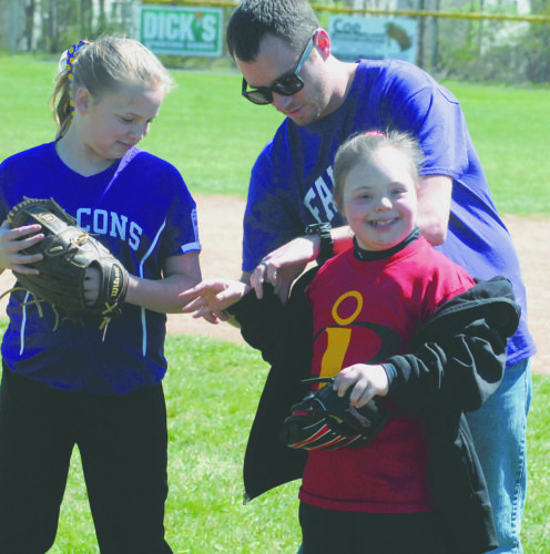 Mallory Burch of the Incredibles gets help from her buddies Cayleigh Laughlin, left, and coach T.J. Bowser on the field during opening day of Hedgesville Little League's Challenger Division.