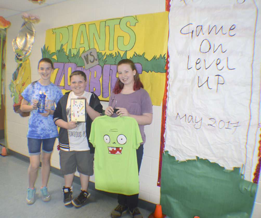 Sixth graders, from left, Taylor McKinney, Jackson Mossolle, and Alaina Fry pose by the plant vs. zombie decorations. (Journal photos by Adranisha Stephens)