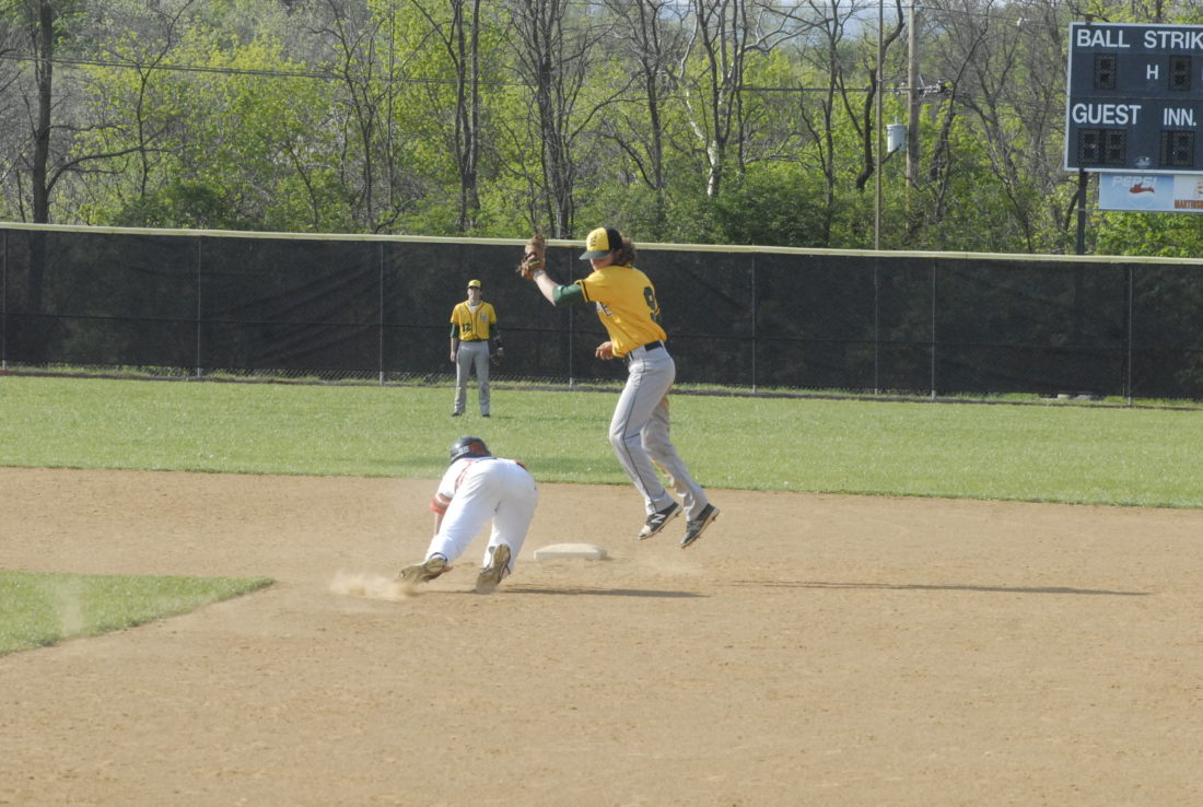 Greenbrier East shortstop Tamer McCallister leaps for a throw on his way to tagging out Martinsburg's Grant Harman on a steal attempt in Friday's game. (Journal photo by Rick Kozlowski)