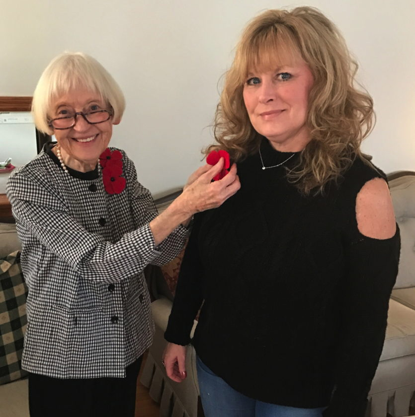 Nancy Myers, Regent of the William Henshaw Chapter, DAR, pinned  handcrafted red felt poppies to her jacket for the program in remembrance of the fallen of World War I. She is pictured pinning one on Jessica Hayes, Vice Regent. (Submitted photo)
