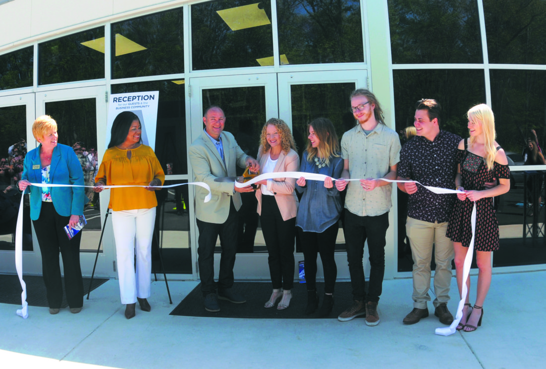 (Journal photo by Ron Agnir) From left, Tina Combs, Jill Upson, Pastors Kevin and Beth Green, Cambra Green, Ethan Green, Emily Schiano DiCola and Mario DiCola cut the ribbon during a ceremony to open the new Airborne Church on Friday morning in Martinsburg.