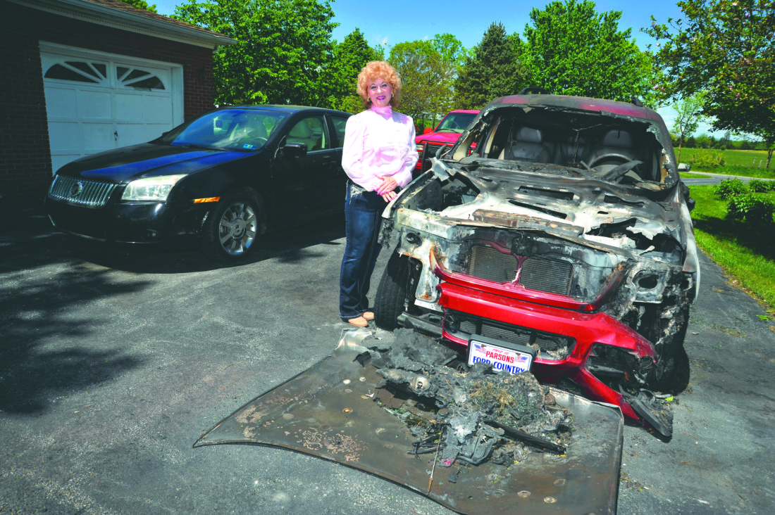 (Journal photo by Jeff McCoy) Phyllis Swartz stands beside her vehicle that was engulfed in flames moments after she returned home from driving it. She credits the Middleway Volunteer Fire Company with saving her home.