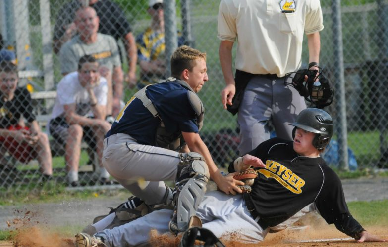 Berkeley Springs catcher Colby Farris, left, tags out Keyser's  Andrew Liller  attempting to score during third-inning action of their Class AA, Region I playoff match last week.