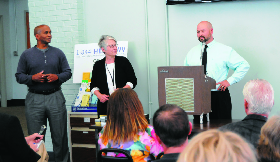 Tim Czaja, director of the day report center, right, speaks at the day report center graduation Monday afternoon in Martinsburg as Dennis Bynum and Vinnie Chacon, Berkeley County Day Report Center recovery coaches listen.