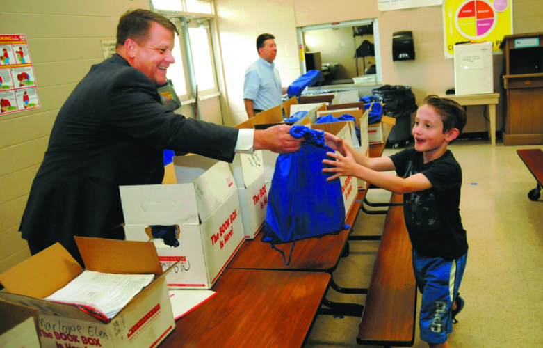 Journal photo by Ron Agnir Charles Lowery of the Martinsburg Sunrise Rotary club, hands a book bag to William Hyman, a second grader at Marlowe Elementary School on Tuesday. Pictured in the background is David Decker. Each bag contained 10 books selected by students last month.