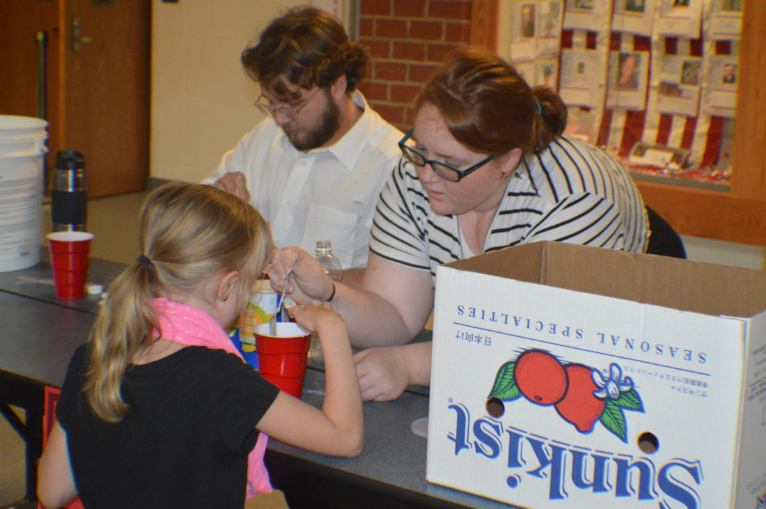 Student helping participant at one of the science booths on STEAM night. (Journal photo by Adranisha Stephens)