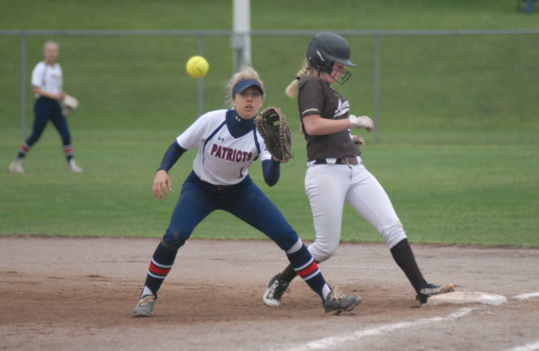 John Marshall's Carli Lightner gets safely back to first base behind the throw to Washington's Jane Cabbiness during Thursday's Class AAA state softball tournament game. (Journal photo by Eric Jones)