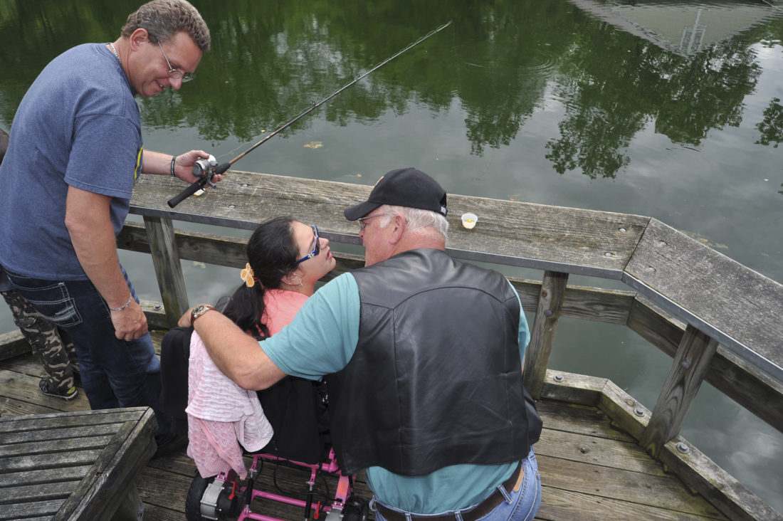 Journal photo by Jeff McCoy Volunteer Biff Rude, left, looks on as Alesa Savage and her grandfather John Krashoc enjoy a day of fishing at the annual fishing derby for special needs children at the Leetown Science Center in Kearneysville.
