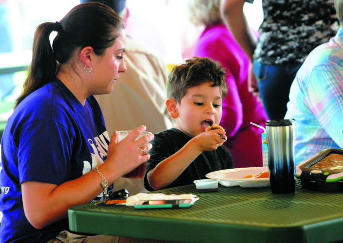 Journal photos by Ron Agnir Michelle Harlow, mom, watches 5-year-old Warren Harlow chomp down on some flapjacks at the Rotary Club of Martinsburg's 8th Annual Pancakes for Polio breakfast Monday morning in Martinsburg.