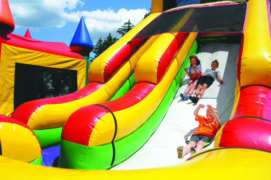 Journal photo by Ron Agnir Second graders Madison Burkhart, Luchlyn Campbell and Calcin take a turn on an inflatable slide at the Rosemont Elementary School end of the year festival on Thursday in Martinsburg.