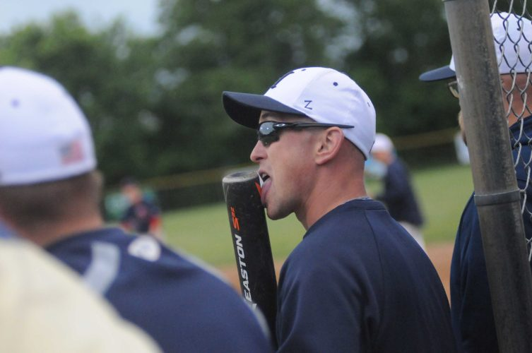 Hedgesville assistant coach J.C. Quinn licks the bat prior to the Eagles trying to key a rally against Washington in the Class AAA, Region IIbaseball tournament. Licking the bat is one of several unique superstitions in the sport.