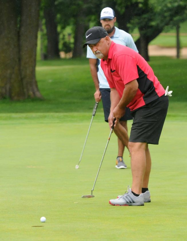 John Reed sinks a 12-foot birdie putt for his team on the ninth hole during the WVU Medicine University Healthcare Foundation Bernie Hutzler Golf Classic Monday afternoon. (Journal photo by Ron Agnir)