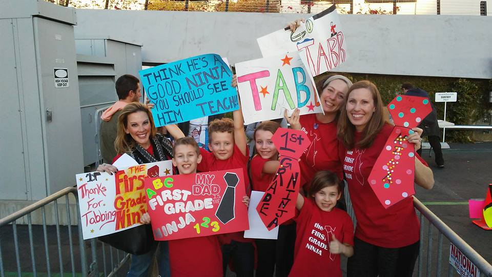 Submitted photo Several of Bobby Tabb's students and co-workers hold up supportive signs prior to his appearance on the television show American Ninja Warrior.