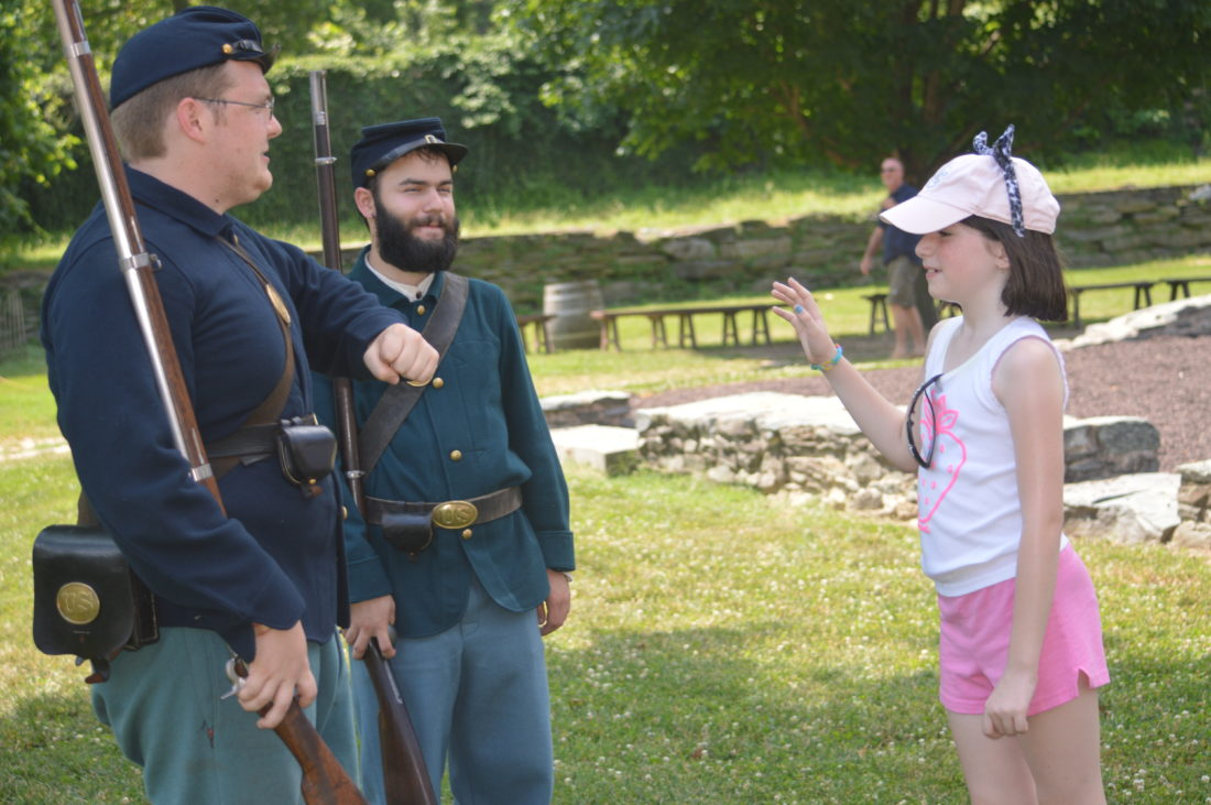 Civil War re-enactors Sam Weathers, left, and Will Levi, right, with Teagan Swyers, 9, teaching her drill practices with a fake rifle.