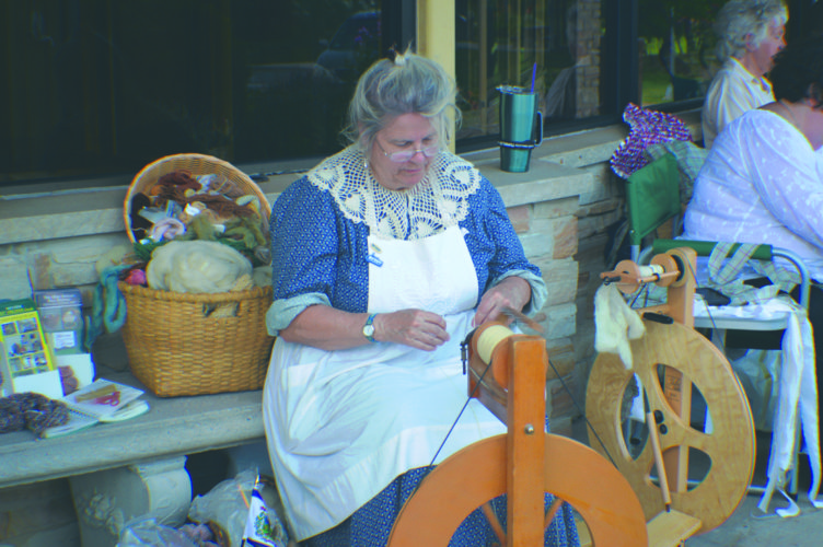 Journal photo Local resident Carol Slovikosky spins wool  at the West Virginia Day Vendor Show on Tuesday.