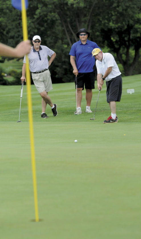 From left: Scramble mates Jeff Rhodes and Eric Mendzela watch as David Camilletti attempts a 35 foot birdie putt on the Par 4 9th hole during the 26th Annual Shenandoah Women's Center Golf Tournament Friday afternoon at Cress Creek County Club in Shepherdstown. (Journal Photo by Ron Agnir)
