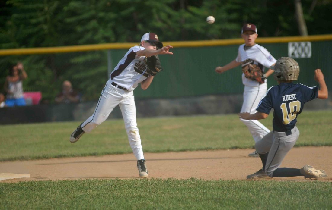 Jefferson's Kellen Kinsler, left, attempts to turn the double play as Hedgesville's Jaxson Ruest slides, trying to break up the play, during Monday's 10-12-year-old District 6, Area 1 elimination game in Hedgesville.