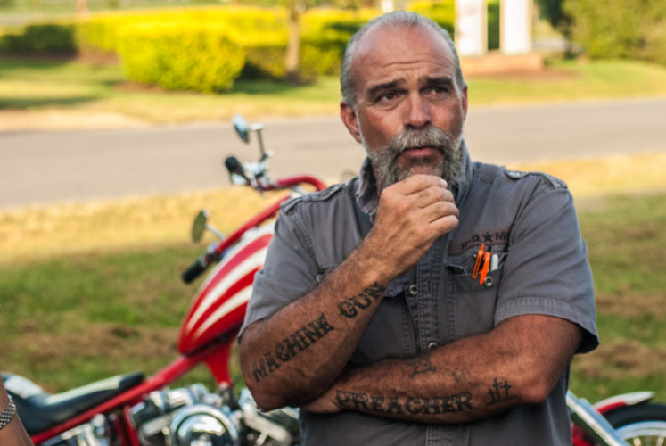 The Machine Gun Preacher, Sam Childers, stands in front of one of his motorcycles.