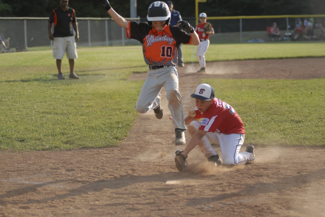 Journal photo by Eric Jones Martinsburg's Ben Reisenweber avoids the tag of Bi-State's Uriah Cutter, right, at home plate during Thursday's District 6 8-10-year-old tournament consolation final.