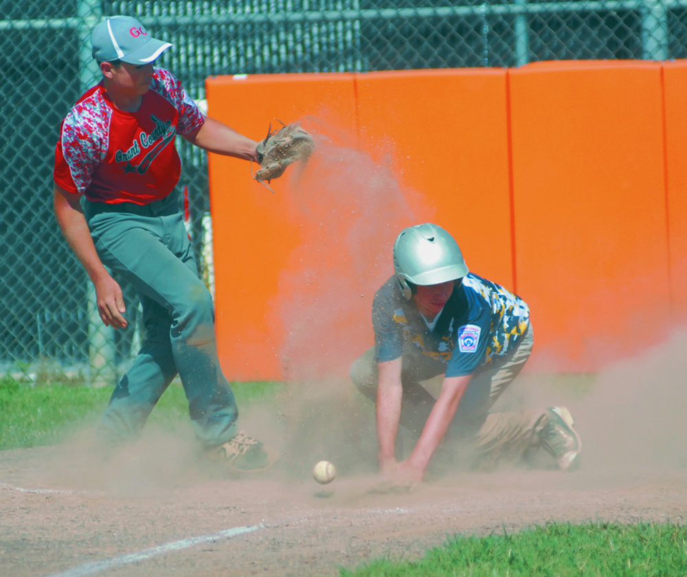Mitchell Miller of Morgan County slides in safely at home plate with his team's first run as Grant County pitcher Montana Sindledecker tries to secure a throw from the catcher. (Journal photo by Rick Kozlowski)