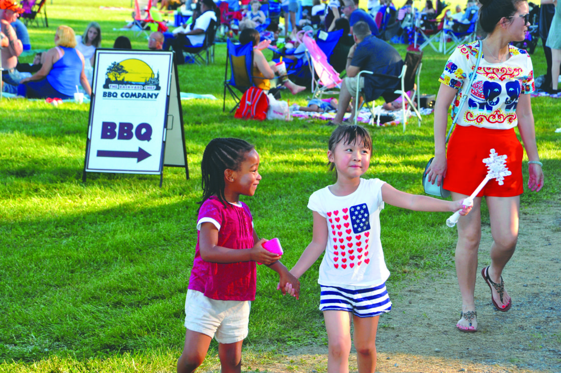 Four-year-old Madison Latimore happily holds hands with 5-year-old Katelyn Zhou as her mother Chrystal Zhou follows closely behind at the Jefferson County Parks and Rec annual fireworks event.