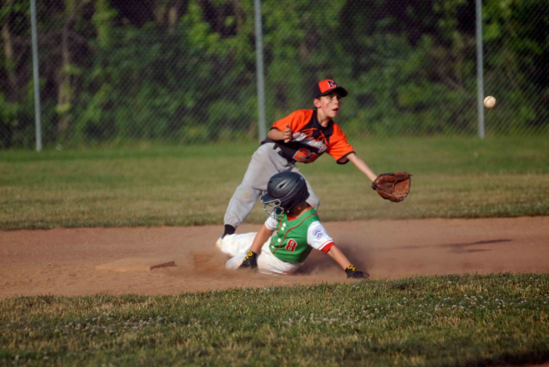 Journal photo by Eric Jones South Berkeley's Kane Whipp slides into second base under Martinsburg Black's Tevis Snow as he awaits a throw during their elimination game on Monday at the Battle at the Burg in Martinsburg.
