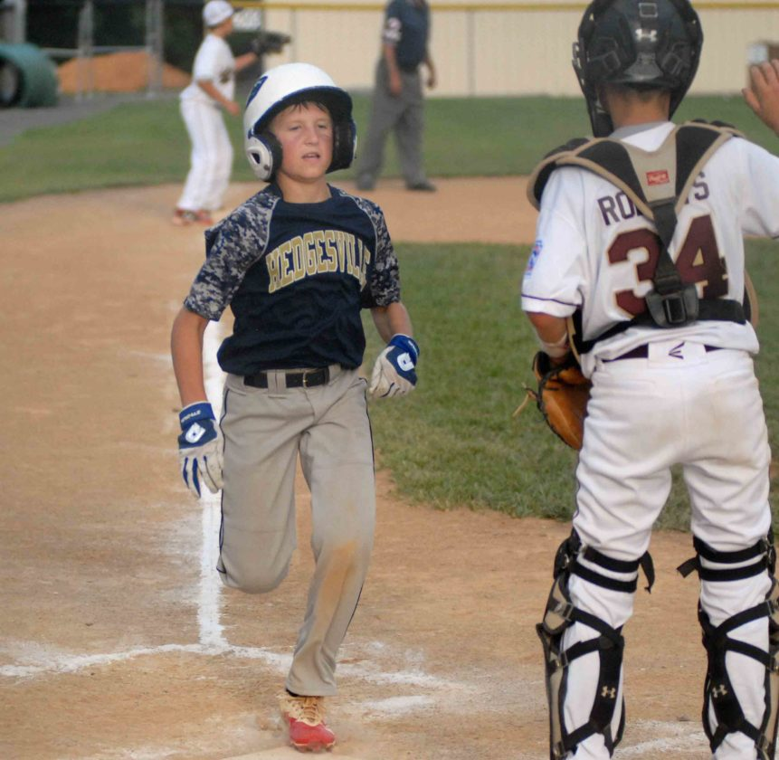 Journal photo by Eric Jones Hedgesville's Nate Noe scores a run as Jefferson catcher Brady Roberts looks on during the fourth inning of Monday's loser's  bracket final of the District 6, 9-11-year-old tournament in Hedgesville.