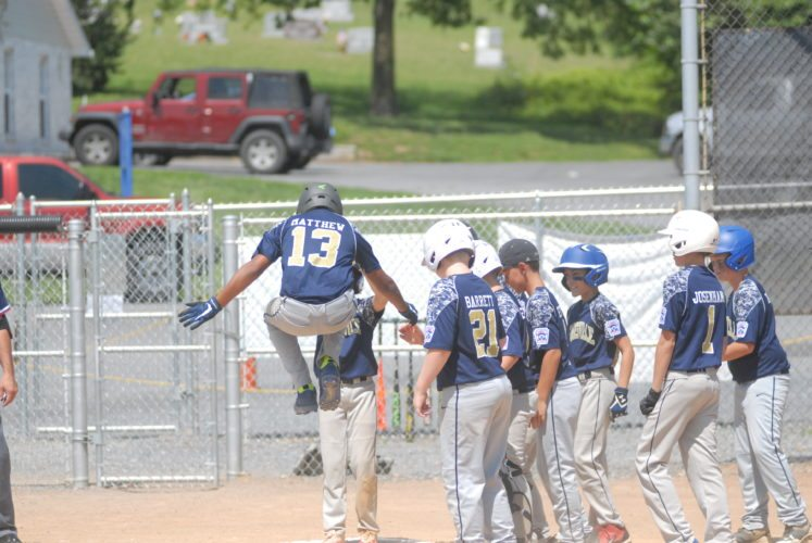 Journal photo by Rick Kozlowski Hedgesville's Tanner Matthew celebrates with teammates after hitting a two-run homer in the first inning of his team's win over Matewan in the 9-11-year-old state baseball tournament on Saturday in Hedgesville.