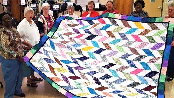 Several of the volunteers who helped make the queen size quilt that will be raffled off to help clients of Meals on Wheels, stand proudly with their work.