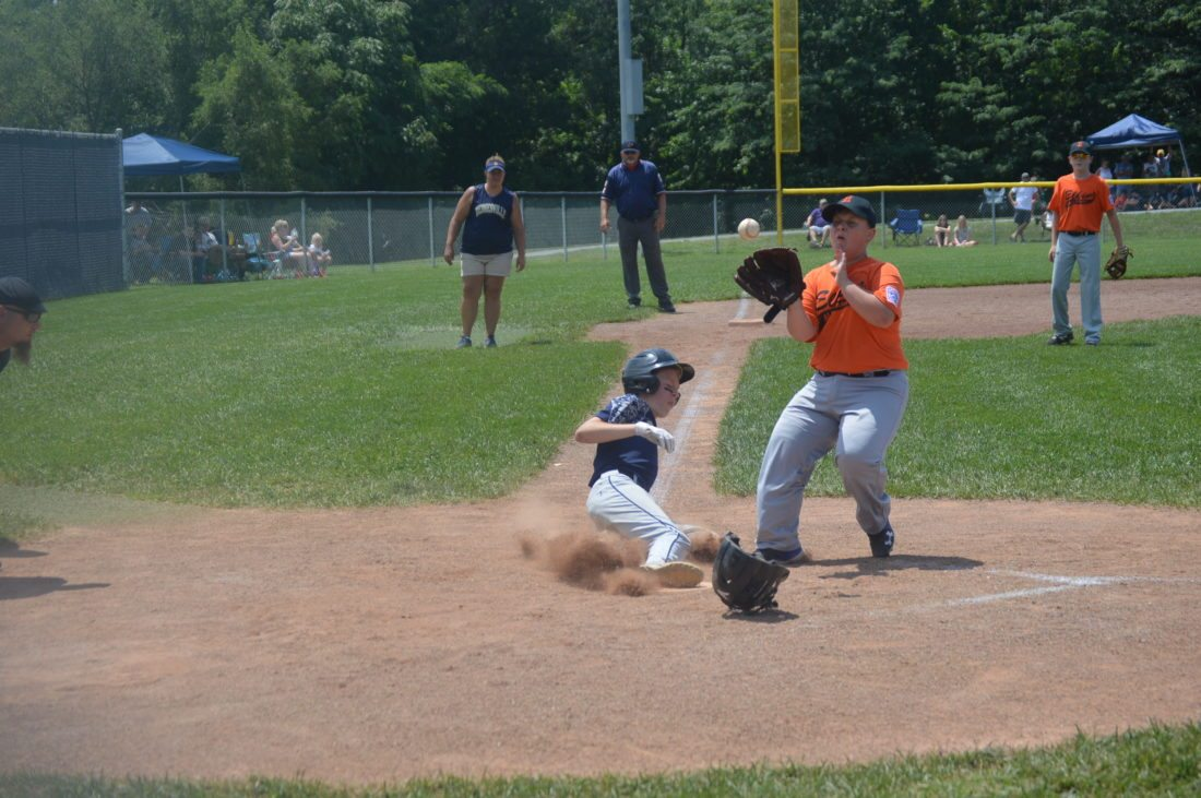 Hedgesville's Aiden Sites, left, scores on a wild pitch as Elkins' Michael O'Dell covers in the third inning of their 9-11-year-old state baseball tournament game on Sunday. Sites was safe as Hedgesville earned an 11-1 win to advance to the quarterfinals.