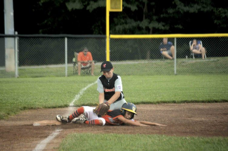 Martinsburg's Isaac Grove, front, slides safely into third on a wild pitch as Chapmanville's Drew Berry applies the tag late during their 9-11-year-old state tournament baseball game Monday at Oatesdale.