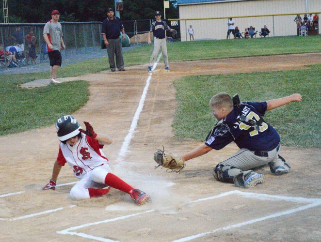 St. Albans' Aiden Youngblood, left, slides into home as Hedgesville's Mason Everhart stretches to try to apply the tag during their 9-11-year-old state tournament baseball game Monday at Hedgesville. Elijah Hamilton singled to right, scoring Youngblood after he reached on a fielder's choice. Hedgesville won 11-7 to earn a spot in the semifinals.