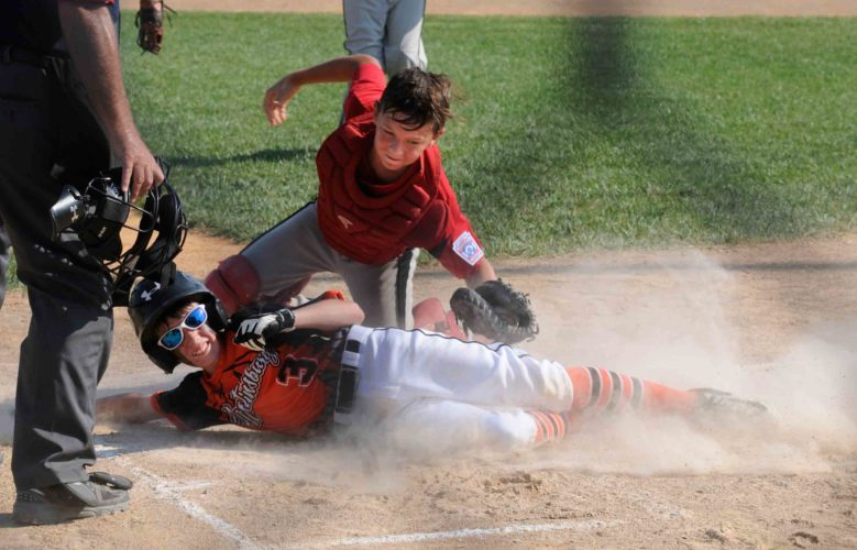Martinsburg's Owen Ruppenthal scores under Worthington catcher Brady Roberts during the first inning of the 9-11 state tournament Tuesday afternoon in Hedgesville. See more photos on CU.journal-news.net.  (Journal photo by Ron Agnir)