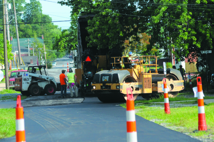 Journal photo by Ron Agnir Workers work to repave a intersection of Samuel Street and West Second Avenue in Ranson on Monday.
