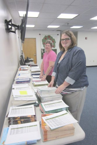 Jada Bennett, on right, reviews with longtime 4-H volunteer Sherry Chambers some of the 743 study projects submitted by Jefferson County's 4-H program student members for this year's Jefferson County Fair. (Submitted photo)