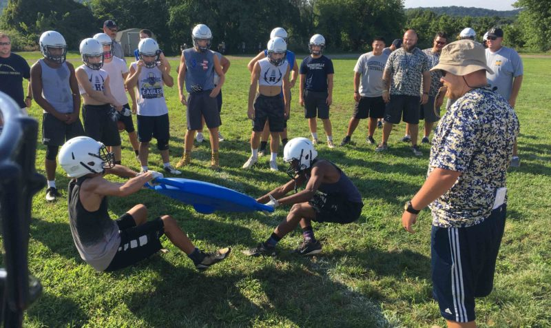 Journal photo by Ron Agnir Hedgesville coach Joey Yurish and players cheer two teammates as they pull in a tug-of-war during football practice on Thursday afternoon in Hedgesville.