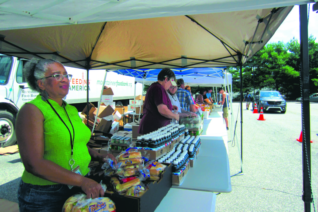 Journal photo by Tim Cook Volunteers distribute food Wednesday during a temporary mobile pantry set up in the parking lot of the West Virginia Health and Human Services office in Charles Town. The mobile pantry was a one-day, pop-up event organized by the regional nonprofit Mountaineer Food Bank in Gassaway, West Virginia.