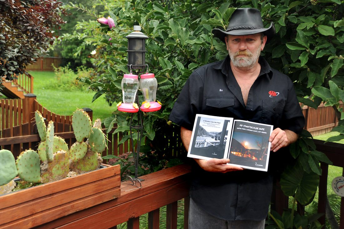 "Author B. Bo Bolyard holds his two books ""A Window Into the Past, The Forgotten History & Secrets of Harpers Ferry, Jefferson County, and The Mountain"" and his second book ""My Spooktacular Home"" at his home in Charles Town."