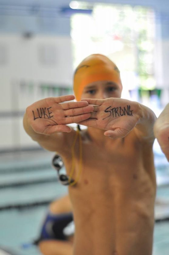 "Submitted photo The words ""Luke Strong"" are seen on a swimmer's hands in support of Luke Bender, a local boy who's battling Cystic Fibrosis."