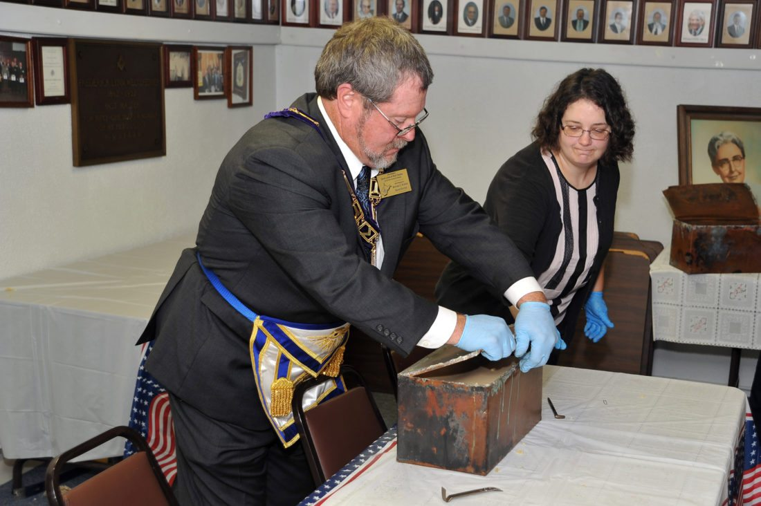 Mason Lodge Grand Master Richard Nuhfer and Shepherd University's Christy Toms, coordinator of archives and special collections, open a time capsule on Saturday from the Sara Cree Hall Cornerstone Casket at the Masonic Lodge in Shepherdstown.