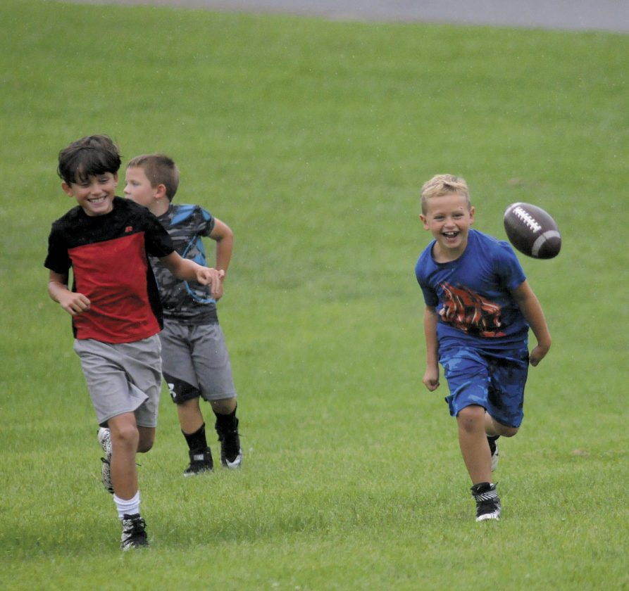 Shown, from left, are 7 year olds Aubrey Burrell, Kaiden Lackey and Carter Young as they play football in the rain Monday afternoon in Martinsburg. (Journal photo by Ron Agnir)